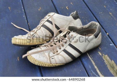 Worn-out sneakers on a weather-beaten blue tabletop - stock photo