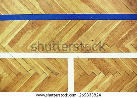 Worn out wooden floor of sports hall with blue and white border lines.  - stock photo