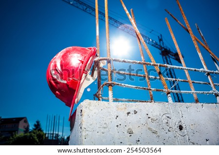 Worn Red Hard Hat reinforced concrete steel with big crane and sun in background on a construction site - stock photo