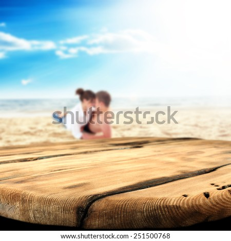 worn table and two lovers on sand and sea landscape  - stock photo