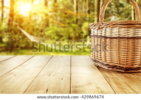 worn table place and picnic basket  - stock photo