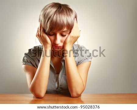 Wornout young woman sitting at desk, isolated on grey - stock photo