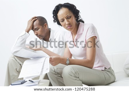 Worried African American couple over domestic bills - stock photo