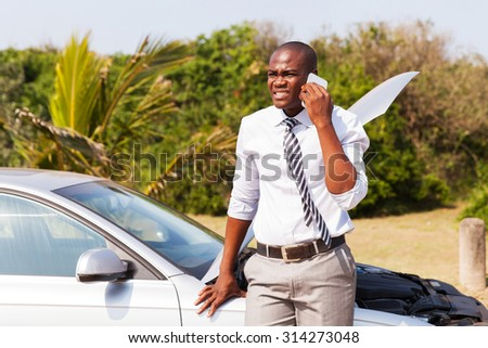 worried african american man with broken car calling for help - stock photo