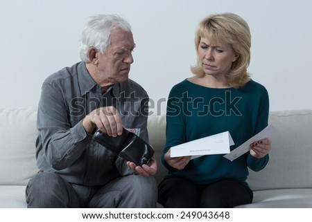 Worried aged marriage checking wallet - stock photo