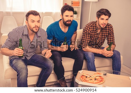 worried and concerned   men watching sport tv with beer and pizza