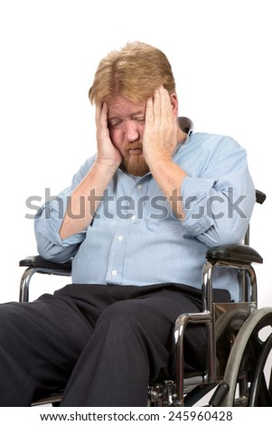 Worried and depressed disabled man in a wheelchair holds his head in his hands. - stock photo