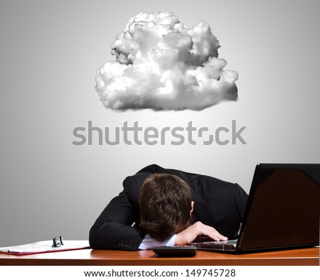 Worried and stressed businessman lying on his desk - stock photo