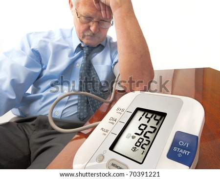 Worried and stressed senior man in shirt and tie (businessman or teacher) showing a high blood pressure reading on the automatic monitor. On white. - stock photo