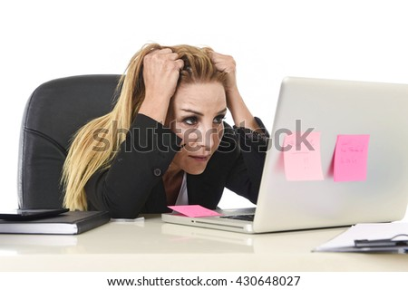 worried attractive businesswoman in stress working with laptop computer at office desk overwhelmed and overworked suffering collapse in frustrated face expression pulling her blond hair