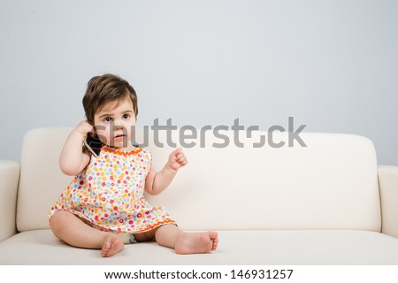 Worried baby sit o a coach and talk by phone
