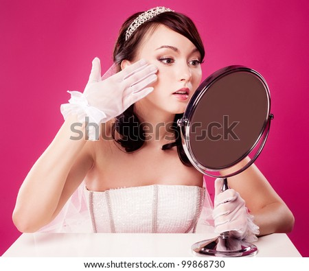 worried bride, sitting by the table with a mirror, isolated against pink studio background - stock photo