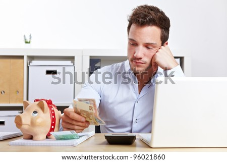 Worried business man with money and piggy bank in office - stock photo