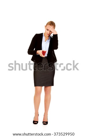Worried business woman looking into her empty wallet - stock photo