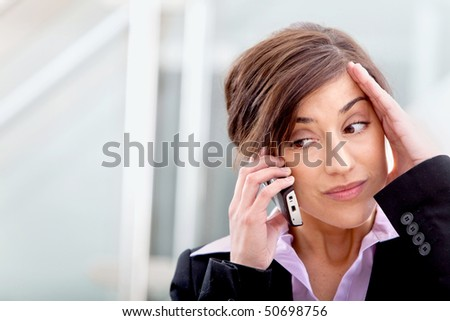 Worried business woman talking on the phone in her office