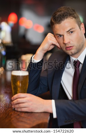 Worried businessman having a drink in a classy bar