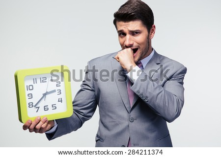 Worried businessman holding clock and looking at camera over gray background - stock photo