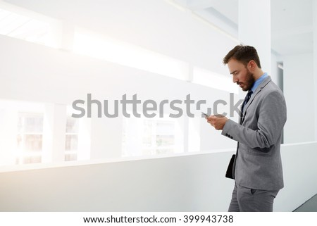 Worried businessman is reading e-mail on mobile phone from investor about suppression of the financing of his project, while is standing in office interior near copy space for your advertising content - stock photo