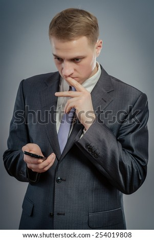 worried businessman reading a text message - stock photo
