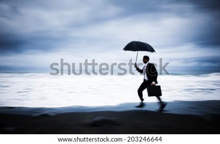 Worried Businessman Running by the Beach - stock photo