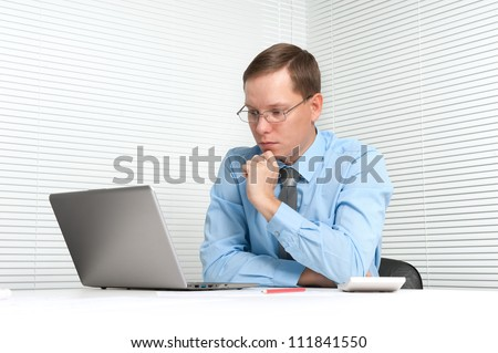 worried businessman sitting at desk with laptop - stock photo