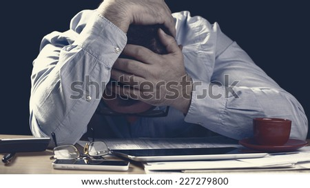 Worried businessman sitting at office desk full of papers being overloaded with work - stock photo