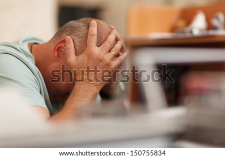 Worried businessman sitting in front of his computer with his head in his hands - stock photo