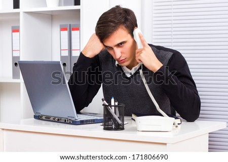 Worried businessman sitting in his office and talking on the phone,Concerned businessman