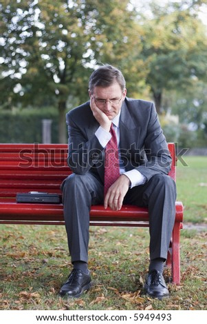 Worried businessman sitting on a red park bench - stock photo