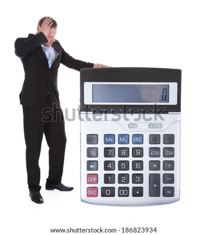 Worried businessman viewing a large calculator as he stands alongside it scratching his head and looking at the digital display  isolated on white - stock photo