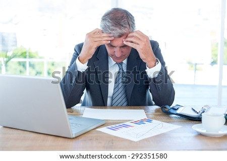 Worried businessman with head in hands in an office - stock photo