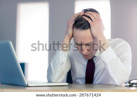 Worried businessman with head in hands in the office