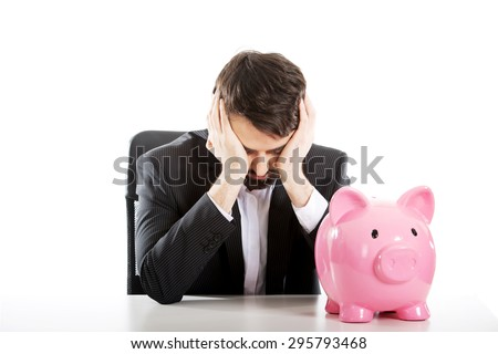 Worried businessman with piggybank by a desk. - stock photo