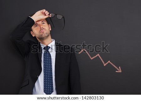 Worried businessman with sign of decreased profit - stock photo