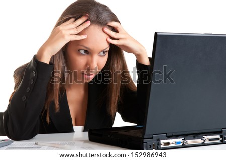 Worried businesswoman looking at a computer screen, isolated in white