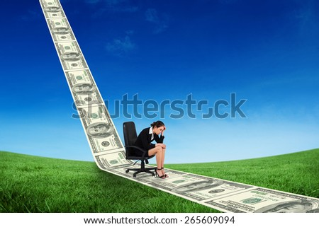 Worried businesswoman on swivel chair against green field under blue sky - stock photo