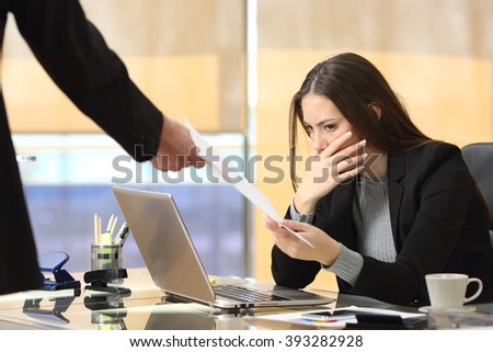 Worried businesswoman receiving a notification from a colleague in her workplace at office - stock photo
