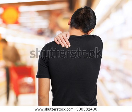 worried chinese man suffering a back ache - stock photo