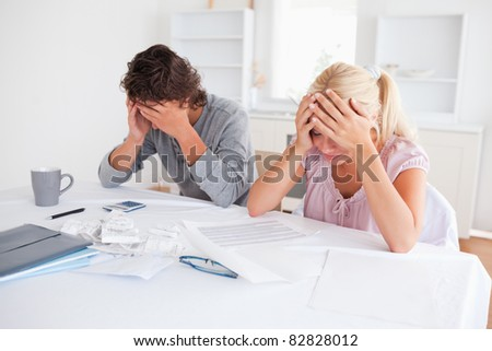 Worried couple doing accountsin their living room