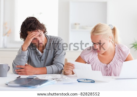 Worried couple doing paperwork in their living room - stock photo