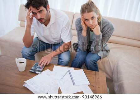 Worried couple doing their accounting in their living room - stock photo
