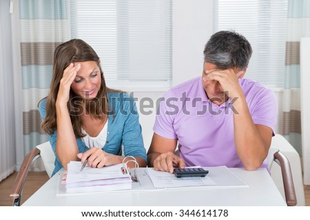 Worried Couple Looking At Unpaid Bills At Home