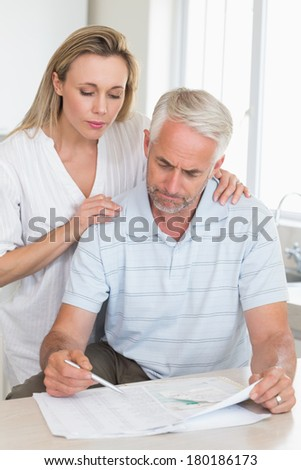 Worried couple working out their finances at home in the kitchen