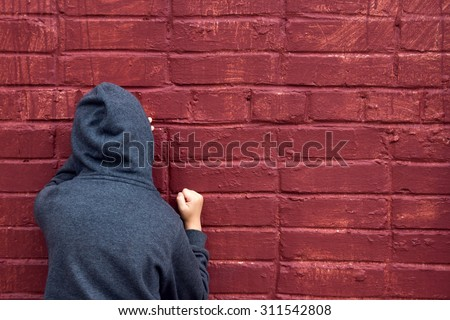 Worried depressed sad teen boy (child) crying near brick wall - stock photo
