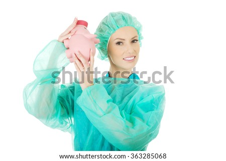 Worried doctor with pink piggy bank. - stock photo