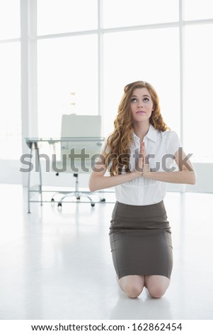 Worried elegant businesswoman kneeling with joined hands in a bright office - stock photo
