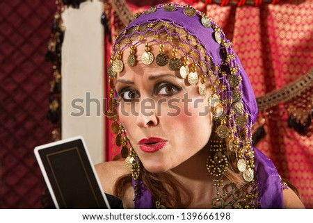 Worried European gypsy fortune teller with tarot card - stock photo