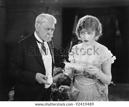 Worried father and daughter looking at a letter