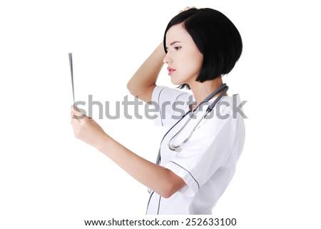 Worried female doctor analysing x-ray image. - stock photo