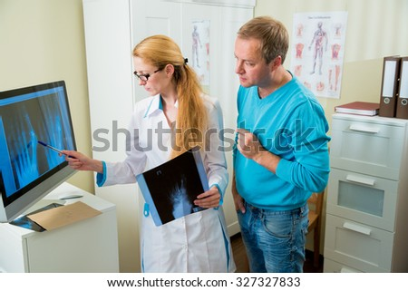 Worried female doctor with handsome male patient looking at x-ray at office. Doctor talking to her patient and showing radiograph.